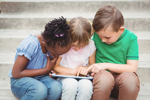 Students sitting on steps and using a tablet on the elementary school grounds