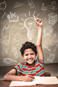 Education doodles against little boy raising hand in classroom