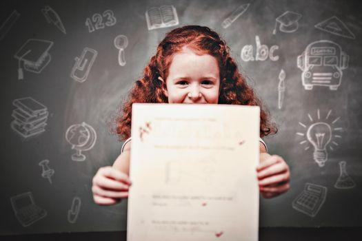 Education doodles against portrait of cute little girl holding paper