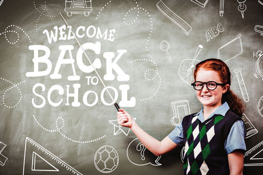 back to school against little girl holding stick in front of blackboard