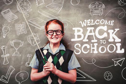 back to school against llittle girl holding stick in front of blackboard