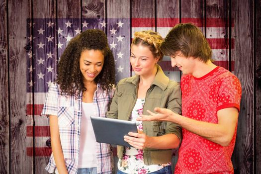 Students using digital tablet in library against composite image of usa national flag