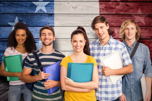 Students holding folders in college against composite image of usa national flag