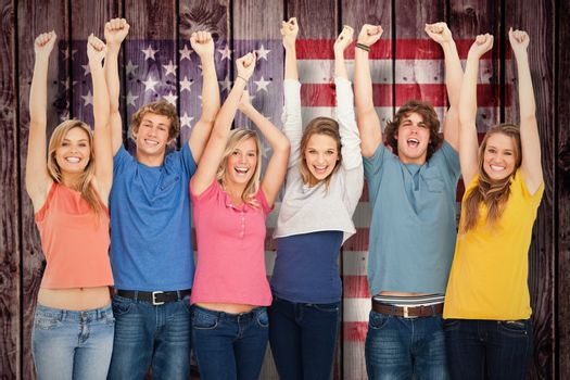 Smiling people raising hands up in the air against composite image of usa national flag