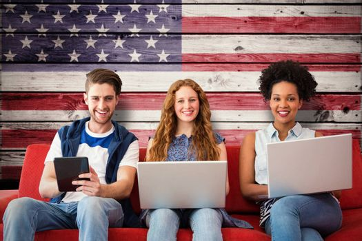 Young adults using electronic devices on couch  against composite image of usa national flag