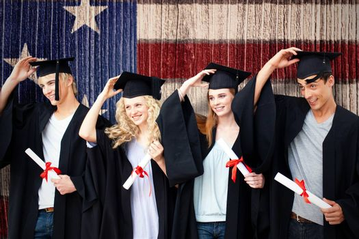 Group of teenagers celebrating after Graduation against composite image of usa national flag