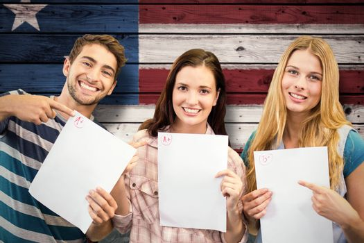 Smiling students showing their exams against composite image of usa national flag