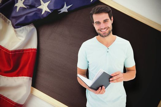 Student holding book against american flag on chalkboard