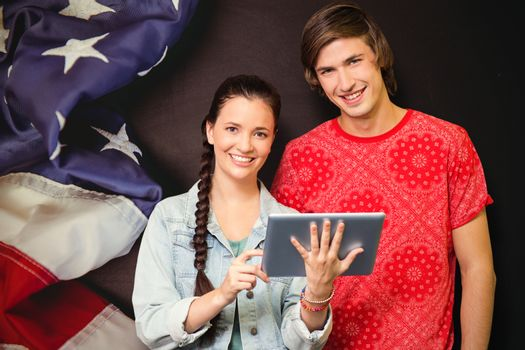 Smiling classmates with tablet pc against american flag on chalkboard
