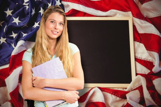 Happy student against american flag on chalkboard