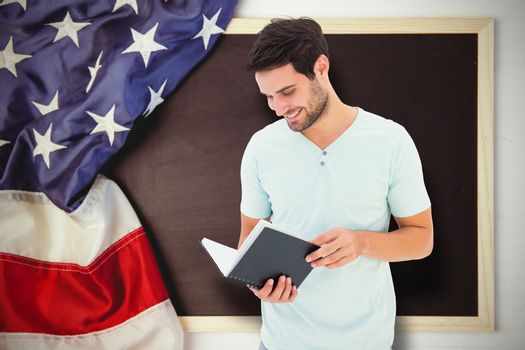 Student reading book against american flag on chalkboard