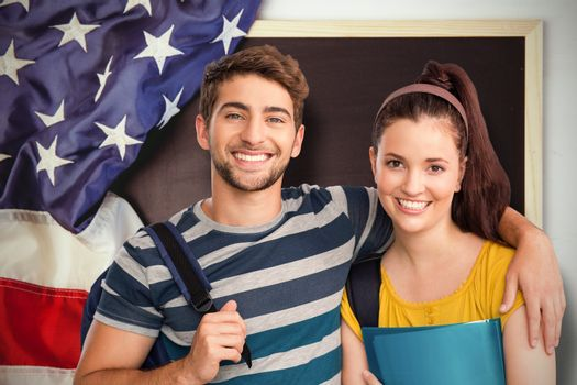 Happy students against american flag on chalkboard