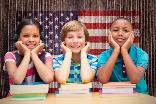 Cute pupils looking at camera in library  against composite image of usa national flag