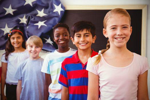 Smiling little school kids in school corridor against american flag on chalkboard