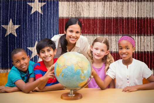 Cute pupils and teacher looking at globe in library  against composite image of usa national flag