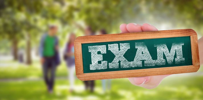 The word exam and hand showing chalkboard against froup of college students walking in the park