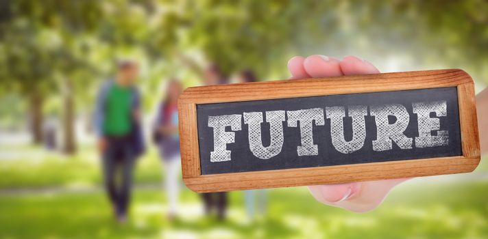 The word future and hand showing chalkboard against froup of college students walking in the park