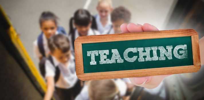 The word teaching and hand showing chalkboard against cute schoolchildren getting on school bus
