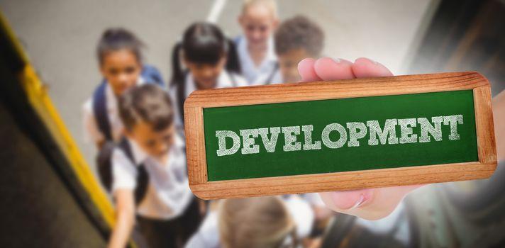 The word development and hand showing chalkboard against cute schoolchildren getting on school bus
