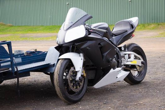A modern racing superbike leaning against its trailer in the paddock at a racetrack.