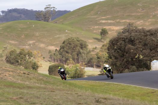 Two superbikes under full power exiting out of a corner.