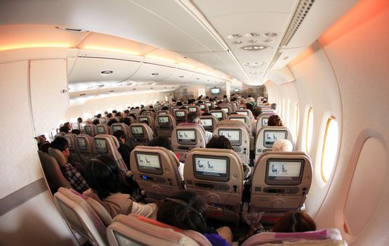 Dubai, United Arab Emirates - March 27, 2012: Travelers are sitting in the interior of the aircraft before take-off look at the instructions
