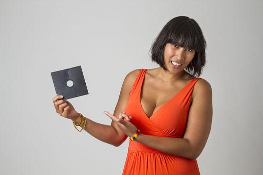Philipino woman wearing a low cut orange dress holding a five inch floppy drive