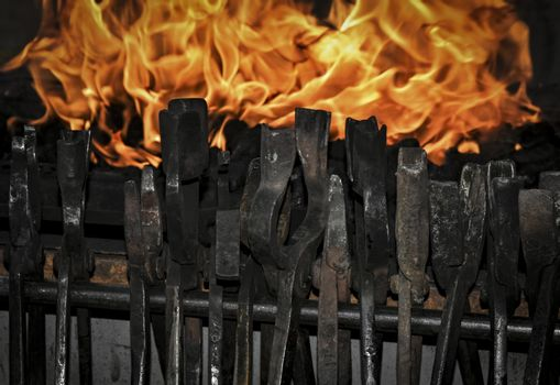 smith tongs in the fire background