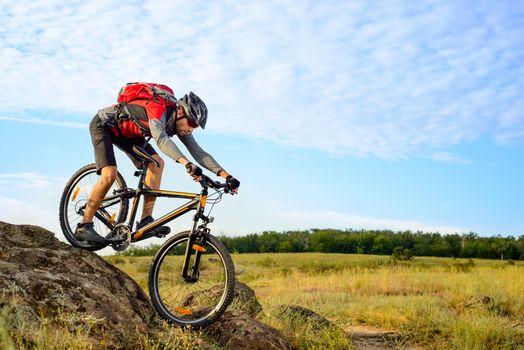 Cyclist Riding the Bike Down Rocky Hill