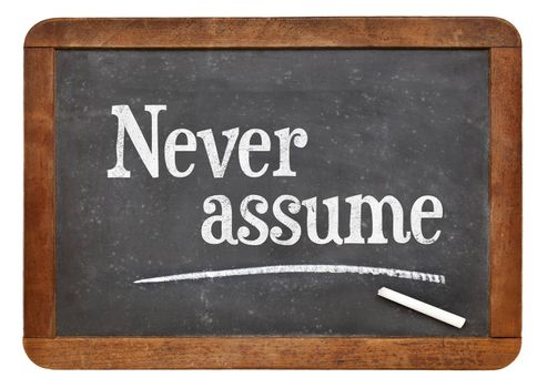 Never assume advice  - text in white chalk on a vintage slate blackboard