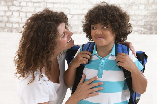 Mother having an conversation with her son before going to school and standing face to face