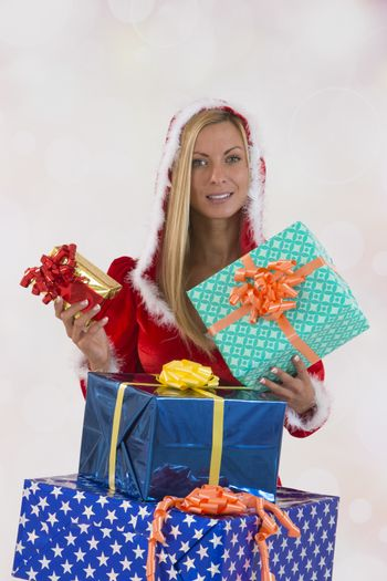 Beautiful young woman in Santa Claus clothes over with gifts