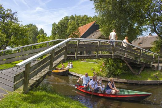 "GIETHOORN, NETHERLANDS - AUGUST 05, 2015: Unknown visitors in the sightseeing boating trip in a canal in Giethoorn. The beautiful houses and gardening city is know as ""Venice of the North""."