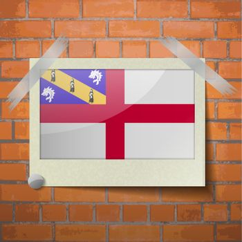 Flags Herm scotch taped to a red brick wall