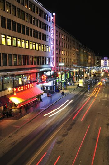 Stockholm, Sweden - December 7, 2013: Night traffic on Kungsgatan in central Stockholm. Cars, pedestrians, taxis in traffic close to the crossing with Sveavagen.