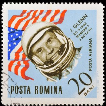 "ROMANIA - CIRCA 1963: A stamp printed in Romania shows USA flag and portrait of astronaut John Glenn, with the same inscription, from the series ""Space Navigation"", circa 1963"