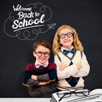 Cute pupils looking at camera against blackboard