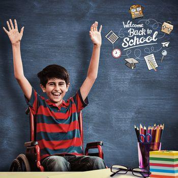 Boy in wheelchair in school corridor against blue chalkboard