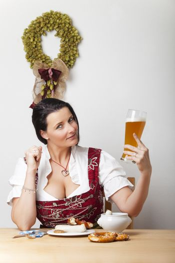 bavarian woman in a dirndl with sausages