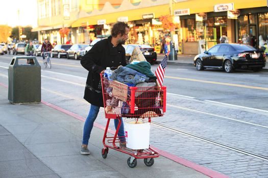 San Francisco, CA, USA - September 24, 2013: Homeless Man with Shopping Cart on the streets in San Francisco. He carries all of his belongings with him in a shopping cart