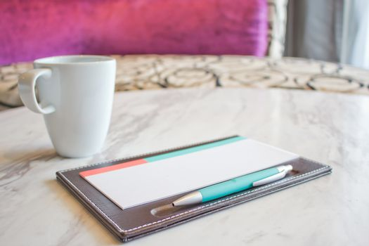 Notebook and white coffee cup on marble table