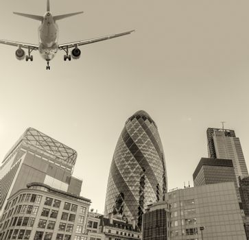 Aircraft landing in London passing over city buildings.