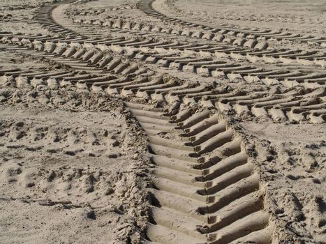 Traces of wheels of a tractor on sand. The filled soil on a platform.