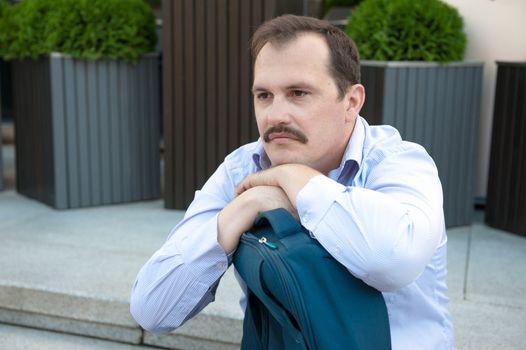 Sad adult man with bag