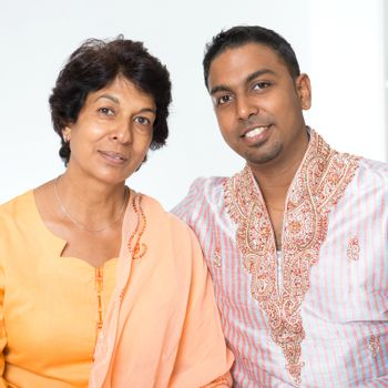 Portrait of happy Indian family at home. Beautiful mature 50s Indian mother and her 30s grown son.