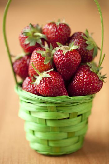 strawberry in green basket on kitchen table