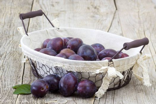 fresh plums in a basket on wooden background