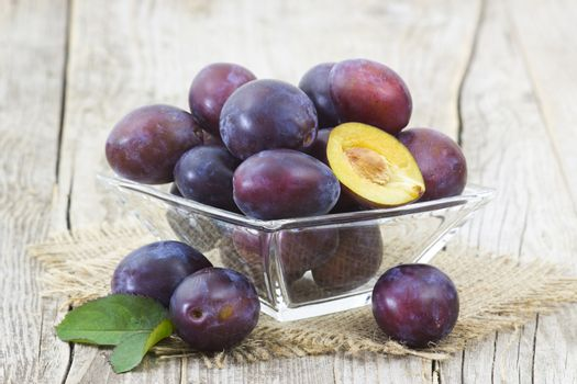 fresh plums in a bowl on old wooden background