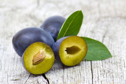 fresh plums on old wooden background