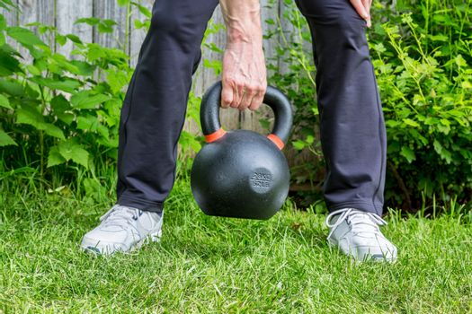 fitness workout with a heavy iron competition kettlebell (62lb/28 kg) on green grass in backyard - outdoor fitness concept